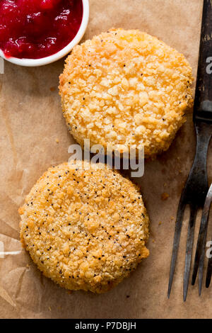 Fried camembert in golden poppy seed breadcrumb, with cranberry& apple sauce - Stock Photo
