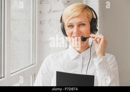 Blonde online consultant woman wears black earphones headset consulting customers standing near rainy window in white office - Stock Photo