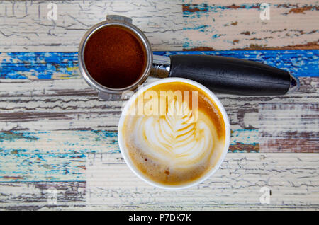 A cup of latte, cappuccino or espresso coffee with milk put on a wood table with dark roasted coffee beans - Stock Photo