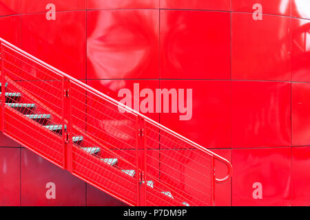 Metal ladder against the background of a red reservoir in an uneven surface - Stock Photo