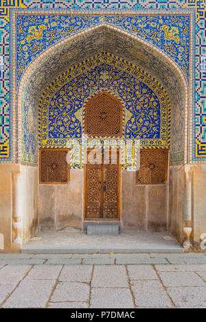 Front on view of a large arch way beautifully decorated in mosaic tiles leading to carved wooden lattice door and window shutters in the Grand Mosque, - Stock Photo