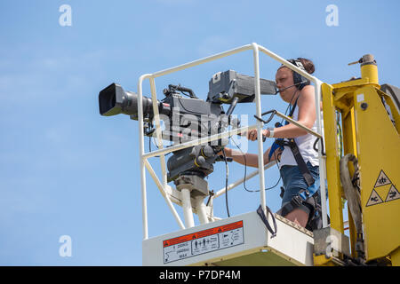 Close up of television camerawoman isolated on elevated platform raised high in midair filming sport event for live broadcast. Blue sky background. - Stock Photo