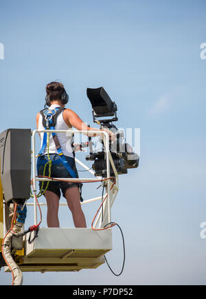Rear view of single television camerawoman on elevated platform raised high in mid air filming sport event for live broadcast. Blue sky background. - Stock Photo
