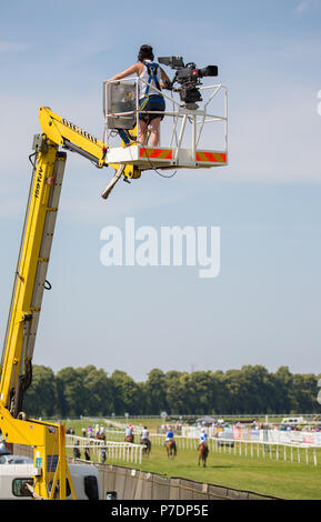 Portrait shot showing television camerawoman on elevated platform, raised high in mid air, filming horse racing live event at Worcester Racecourse, UK - Stock Photo