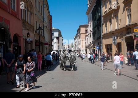Horse and carriage taking tourists around Krakow City Centre, Krakow, Poland, Europe. - Stock Photo