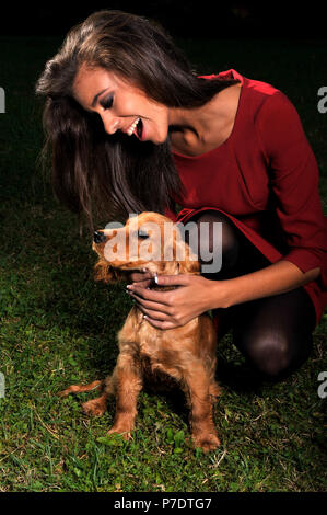 young girl dressed in red plays happy with her dog English Cocker Spaniel smiling - Stock Photo