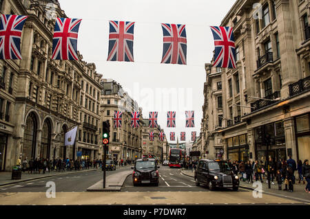 LONDON, UK - APRIL 2018: Red buses and taxis passing under union Jack flags before Royal wedding in Regent street. - Stock Photo