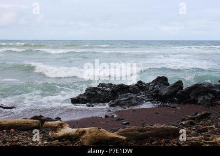 Waves from the Pacific Ocean rolling into Koki Beach, a black and red sand beach in Hana, Maui, Hawaii, USA - Stock Photo