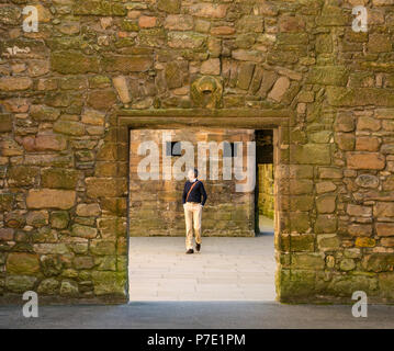 Male tourist framed by doorway walking through ruined palace, Linlithgow  Palace, West Lothian, Scotland, UK - Stock Photo