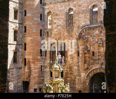Ruined interior central courtyard with family standing in ruined window frame, Linlithgow Palace, West Lothian, Scotland, UK - Stock Photo