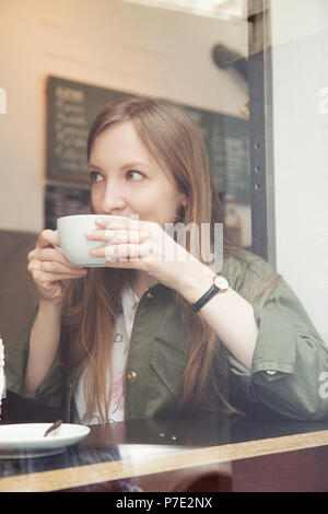Young woman having coffee in cafe - Stock Photo