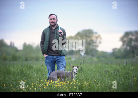 Young man with his dog in field, portrait