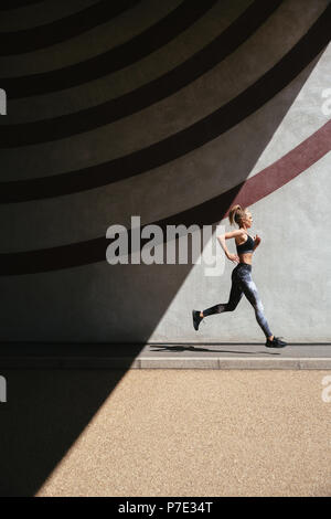 Young woman running, patterned background - Stock Photo