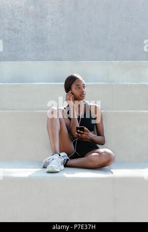 Young woman listening to music on mobile phone - Stock Photo