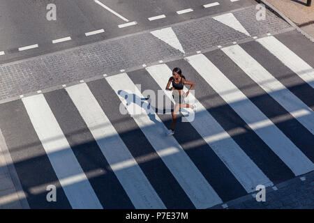 Young woman running on zebra crossing - Stock Photo