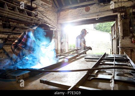 Senior blacksmith and son welding metal on workbench in blacksmiths shop - Stock Photo