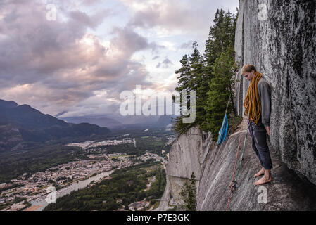 Young male climber standing barefoot on bellygood ledge, The Chief, Squamish, Canada - Stock Photo