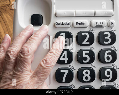 Visually impaired elderly woman dialling NHS 111 help line on big button telephone. - Stock Photo