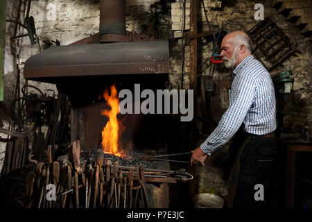Blacksmith heating metal in forge fire in blacksmiths shop - Stock Photo