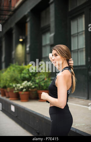 Portrait of woman wearing workout clothes looking away, New York, USA - Stock Photo
