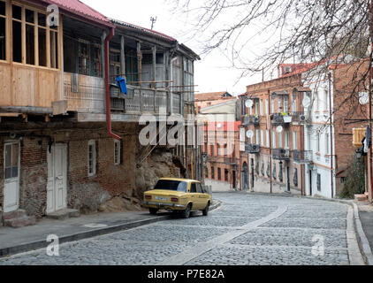 Old car parked along a cobblestone street in Tbilisi old town district, Georgia - Stock Photo