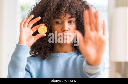 African american woman holding golden bitcoin cryptocurrency at home with open hand doing stop sign with serious and confident expression, defense ges - Stock Photo