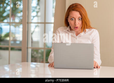 Redhead woman using computer laptop at home scared in shock with a surprise face, afraid and excited with fear expression - Stock Photo