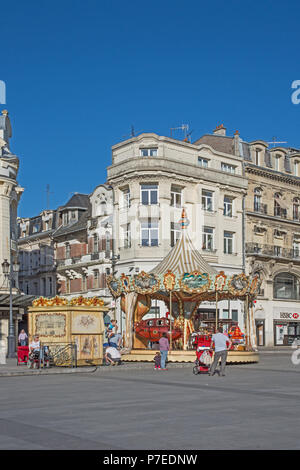Charming old fashioned traditional carousel children's roundabout in Place de l'Hotel de Ville St Quentin Aisne France - Stock Photo