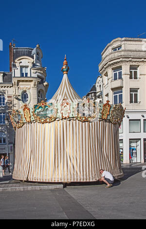 Charming old fashioned traditional carousel children's roundabout being closed up for the night in Place de l'Hotel de Ville St Quentin Aisne France - Stock Photo