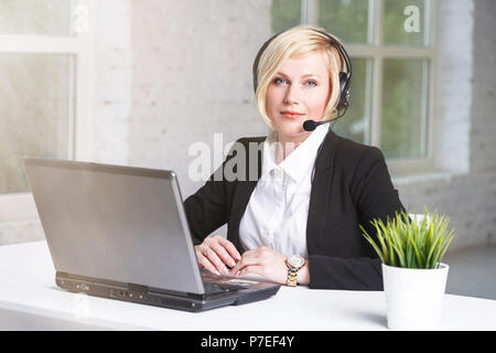 Beautiful blonde adult woman call center operator dressed in black stylish suit working in white wide office on table with laptop - Stock Photo