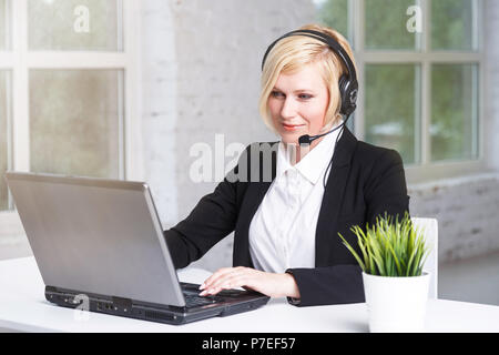 Beautiful blonde adult woman call center operator dressed in black stylish suit working in white office on table with laptop - Stock Photo