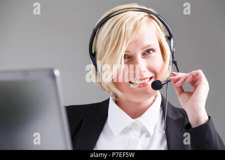 Smiling woman, call center operator dressed in black stylish suit with headset earphones - Stock Photo