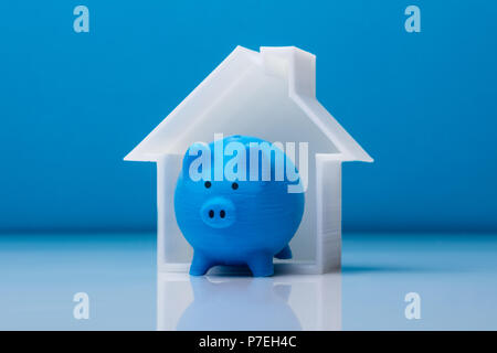 Close-up Of Piggybank And House Model In Front Of Blue Background - Stock Photo