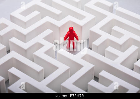 Close-up Of Red Human Figure Standing In The Centre Of White Labyrinth - Stock Photo