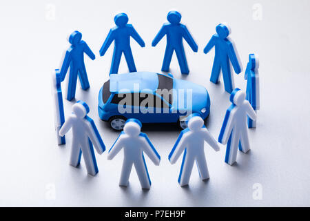 Elevated View Of Blue Car Surrounded By Human Figures On White Background - Stock Photo