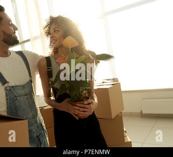 Close-up of a beautiful young couple is carrying things into a new home - Stock Photo