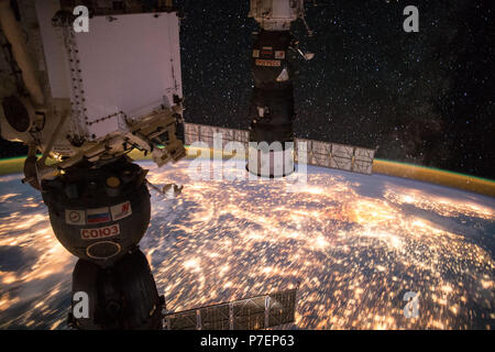 Earth observation taken during a night pass by the Expedition 49 crew aboard the International Space Station (ISS). Docked Soyuz and Progress spacecraft visible. - Stock Photo