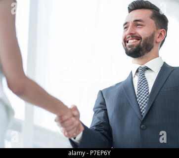 Image of business partners handshaking in office - Stock Photo