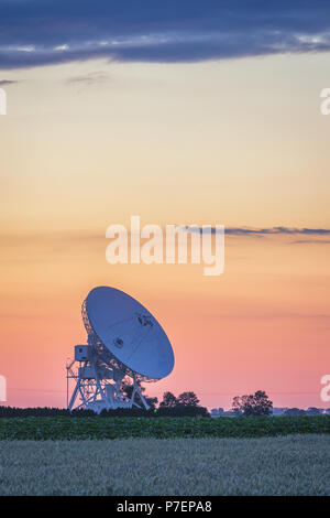 Pastel colors on the sky during summer sunset over radiotelescope antenna - Stock Photo