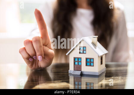 Close-up Of A Businesswoman Gesturing No Sign Near House Model On Desk - Stock Photo