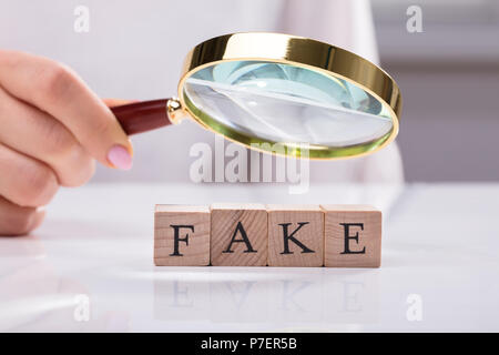 Close-up Of A Businesswoman's Hand Examining Wooden Blocks Showing Fake Word - Stock Photo