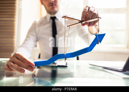 Businessperson's Hand Manipulating Blue Arrow With Rope - Stock Photo
