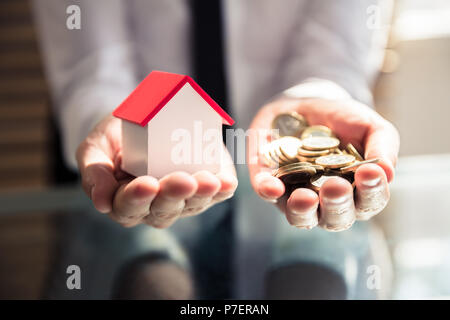 Close-up Of A Businessperson's Hand Holding House Model And Golden Coins - Stock Photo