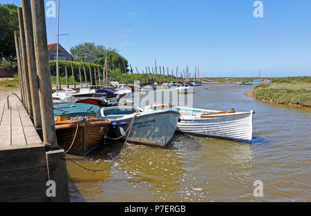 A view of small boats moored at the west end of the harbour on the North Norfolk coast at Blakeney, Norfolk, England, United Kingdom, Europe. - Stock Photo