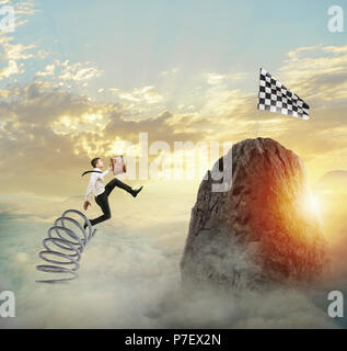 Businessman jumping on a spring to reach the flag. Achievement business goal and Difficult career concept - Stock Photo