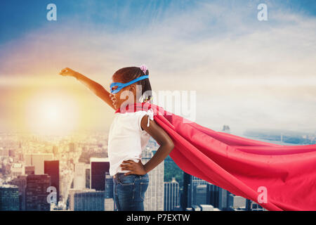 Child acts like a superhero to save the world - Stock Photo