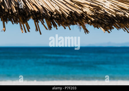 Beach umbrella and sea in the background. Selective focus. Close up. - Stock Photo