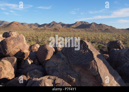 Spiral Hohokam petroglyph on Signal hill with Saguaros and mountains in the background in Saguaro National Park near Tucson, Arizona, United States. - Stock Photo