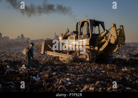 A picker following a front loader collecting recyclable refuse at the Robinson Deep landfill in South Africa's commercial capital of Johannesburg - Stock Photo