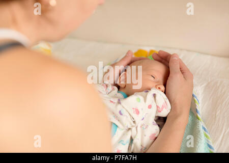 Mother comforting her a newborn baby after changing diapers - Stock Photo